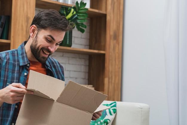 Uomo allegro con pacco aperto