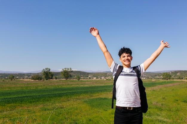 Uomo allegro del viaggiatore con la mano sollevata che sta nel campo verde