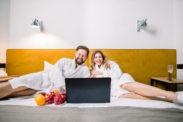 Uomo allegro e donna bionda felice che esaminano computer portatile nella camera di albergo e che guardano film, sorridenti e ridenti