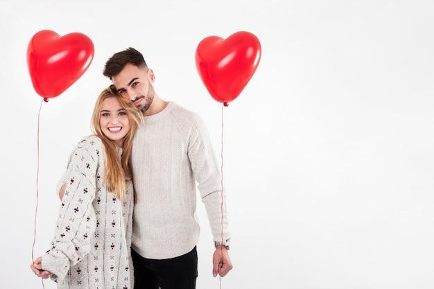 Uomo allegro e donna in posa con palloncini
