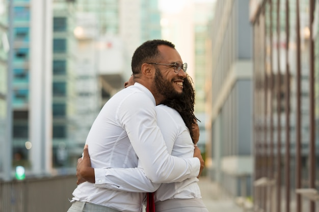 Uomo allegro felice di affari che abbraccia amico femminile