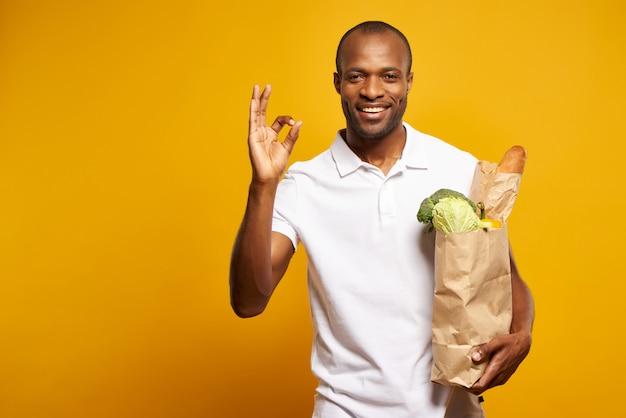 Uomo americano con la borsa di prodotti freschi che mostrano il gesto ok.