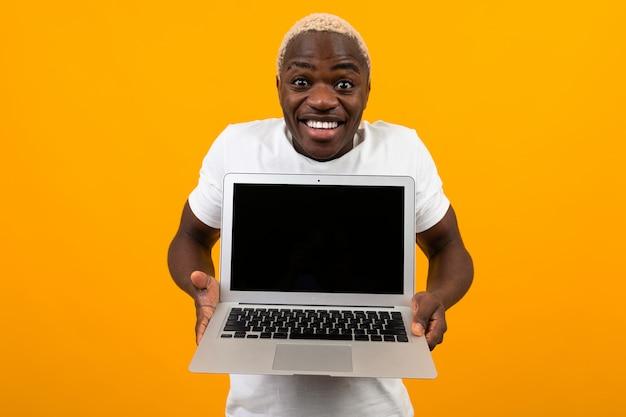 Uomo americano sorpreso allegro attraente in una maglietta bianca con un bel sorriso allunga le braccia con un computer portatile con un layout su un giallo