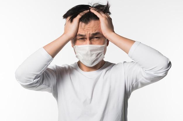 Uomo ammalato sconcertato che indossa maschera medica