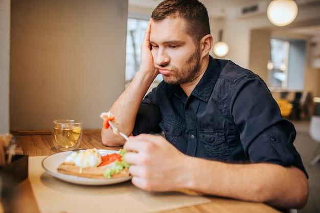 Uomo annoiato e triste è seduto al tavolo e al caffè. ha in mano un pezzo di verdura sulla forchetta. l'uomo lo sta guardando ed espirando.