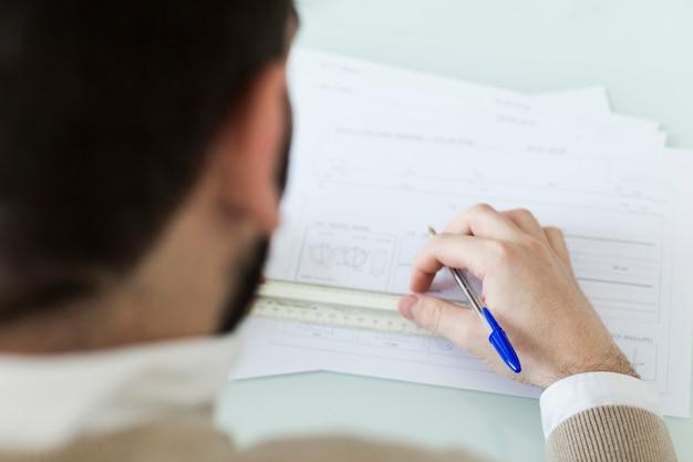 Uomo anonimo che sottolinea i dati nei documenti