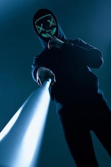 Uomo anonimo con mazza da baseball in una felpa con cappuccio nera e maschera al neon