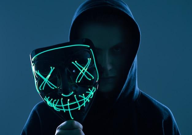 Uomo anonimo in felpa con cappuccio nera che nasconde il viso dietro una maschera al neon