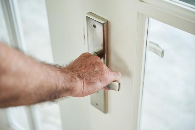 Uomo anonimo ritagliato che tiene la maniglia della porta per aprire la porta
