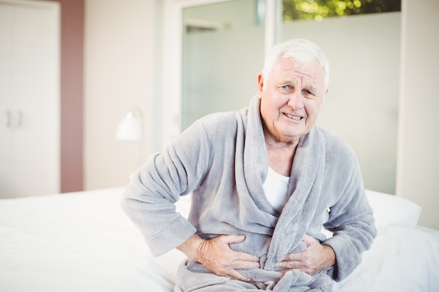 Uomo anziano accigliato con mal di stomaco