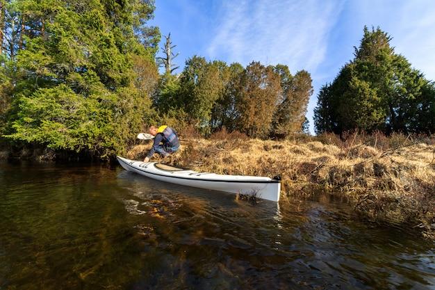 Uomo anziano adulto in procinto di entrare nel suo kayak bianco