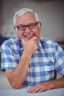 Uomo anziano allegro al tavolo