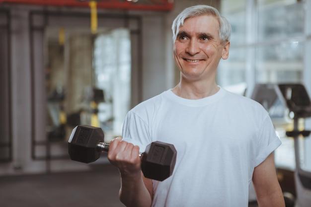 Uomo anziano allenandovi in palestra