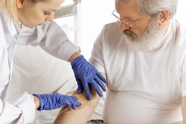 Uomo anziano anziano che recupera in un letto di ospedale isolato su bianco