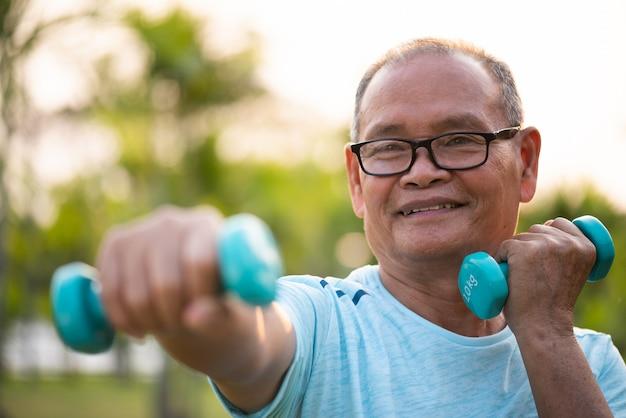 Uomo anziano asiatico che fa esercizio fisico all'aperto con le teste di legno