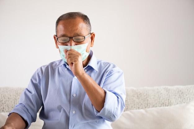 Uomo anziano asiatico che indossa maschera protettiva e tosse. concetto di assistenza sanitaria senior.