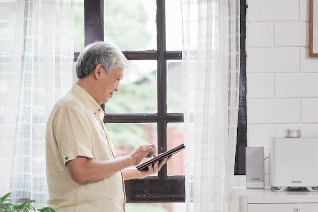 Uomo anziano asiatico che utilizza compressa che controlla media sociali vicino alla finestra in salone a casa. concetto degli uomini senior di stile di vita a casa.