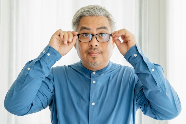 Uomo anziano asiatico di affari con i vetri d'uso dei capelli grigi e lavorare nell'ufficio