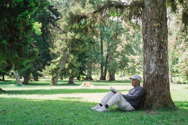 Uomo anziano asiatico senior che legge un libro all'aperto