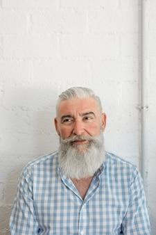 Uomo anziano barbuto alla moda in camicia in salone