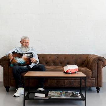 Uomo anziano barbuto che si siede nel negozio di barbiere