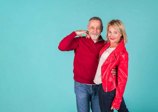 Uomo anziano che abbraccia la sua ragazza in piedi su sfondo turchese