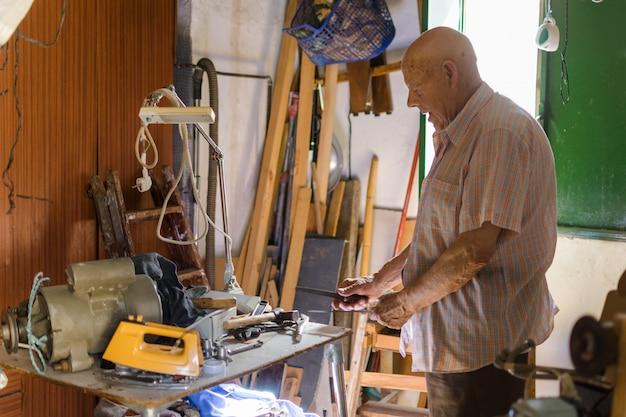 Uomo anziano che affila un coltello con una calce