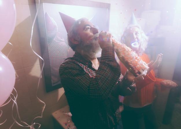 Uomo anziano che beve l'alcool attraverso la bottiglia con la sua moglie che getta i coriandoli nell'aria