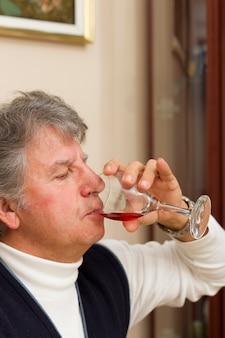 Uomo anziano che beve vino rosso