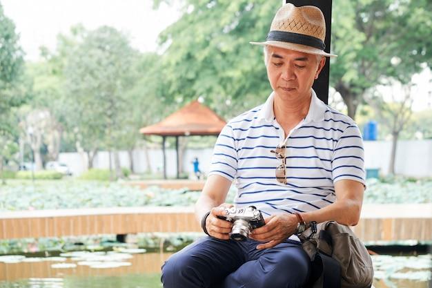 Uomo anziano che controlla la sua macchina fotografica