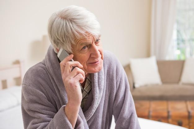 Uomo anziano che fa una telefonata sul letto