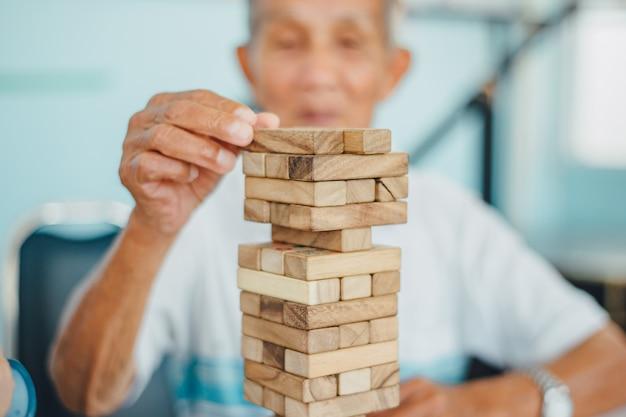 Uomo anziano che gioca a blocchi di legno per prevenire la demenza e la malattia di alzheimer.