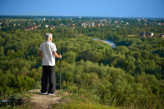 Uomo anziano che guarda bello panorama che tiene i bastoni di inseguimento.