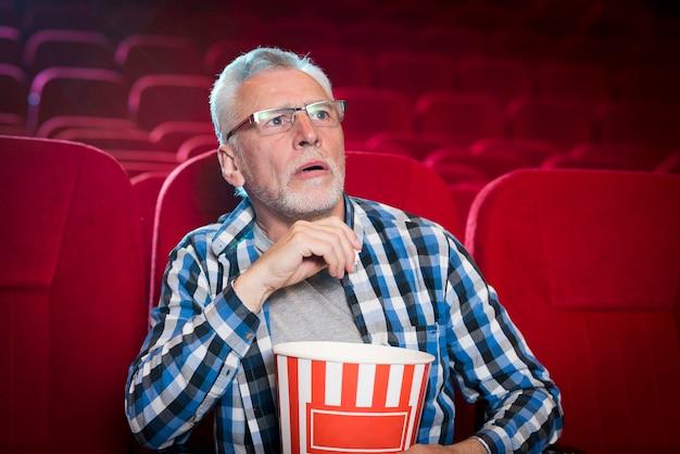 Uomo anziano che guarda film nel cinema