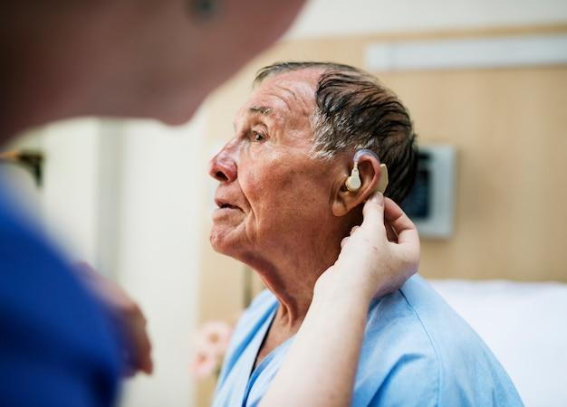 Uomo anziano che indossa un apparecchio acustico