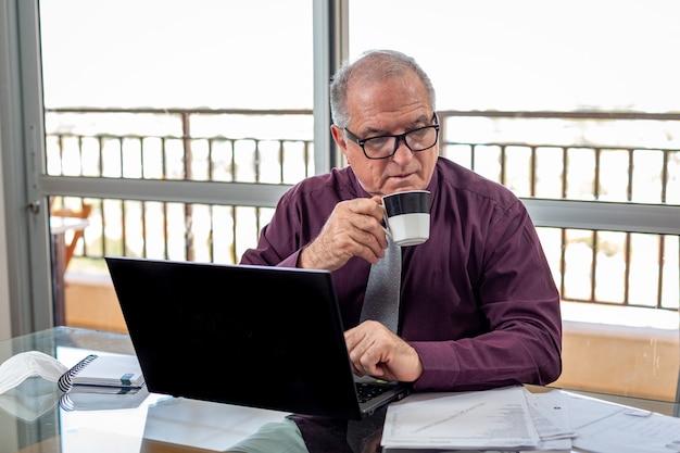 Uomo anziano che lavora a casa durante la pandemia