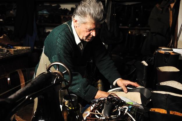 Uomo anziano che lavora con la vecchia macchina nel suo laboratorio