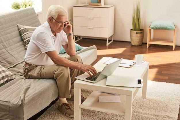 Uomo anziano che lavora da casa