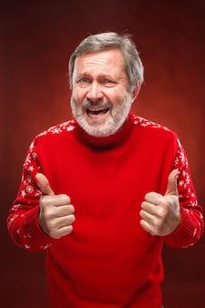 Uomo anziano che mostra sospiro giusto su rosso