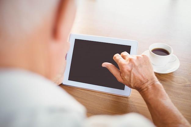 Uomo anziano che per mezzo della compressa e bevendo caffè a casa