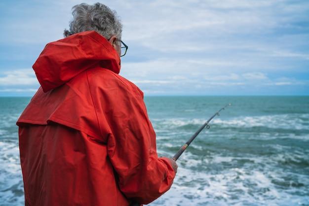 Uomo anziano che pesca nel mare.