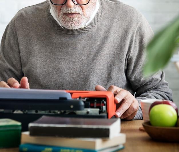 Uomo anziano che scrive su una macchina da scrivere