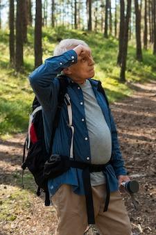 Uomo anziano che si stanca mentre è in viaggio con lo zaino in spalla nella natura