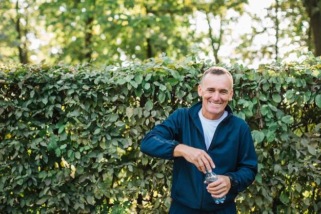 Uomo anziano che sorride mentre tenendo una bottiglia d'acqua in mano