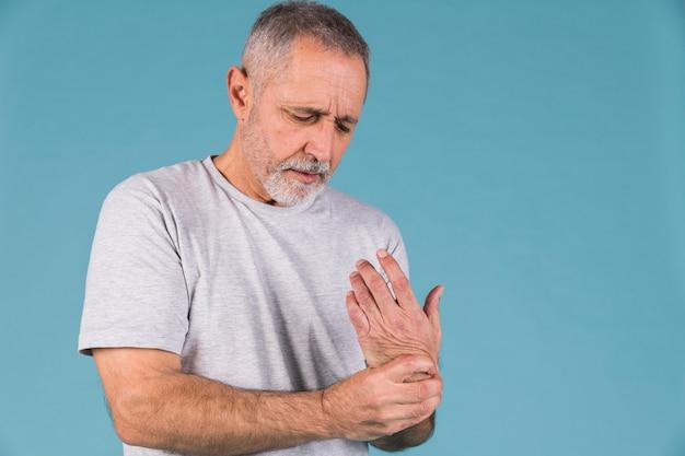 Uomo anziano che tiene il polso doloroso
