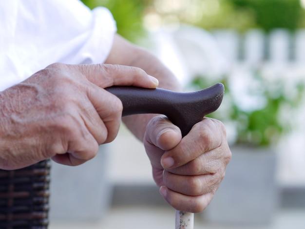 Uomo anziano che tiene un bastone