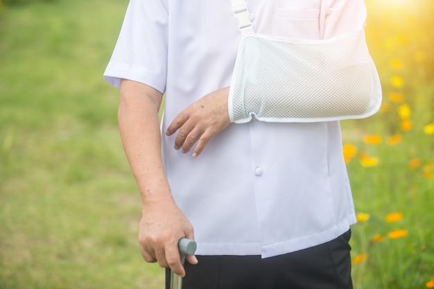 Uomo anziano che tiene un braccio rotto della canna dopo l'incidente con la stecca del braccio di usura nel parco