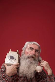 Uomo anziano che tiene un telefono