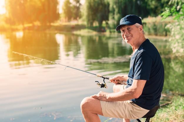 Uomo anziano con capelli grigi pesca sul fiume in estate.