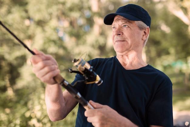 Uomo anziano con gray hair fishing sul fiume di estate.